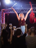 Female performer with arms raised singing during music event